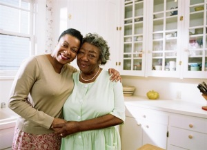 A middle-aged woman and an elderly woman hugging in a kitchen
