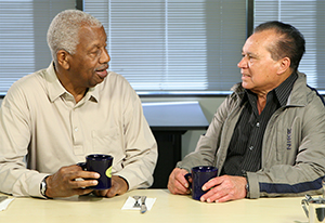 Two men talking and drinking coffee.
