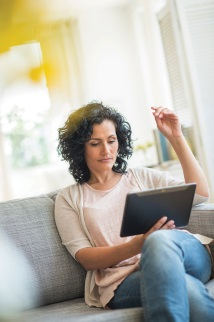Woman sitting on couch looking at laptop